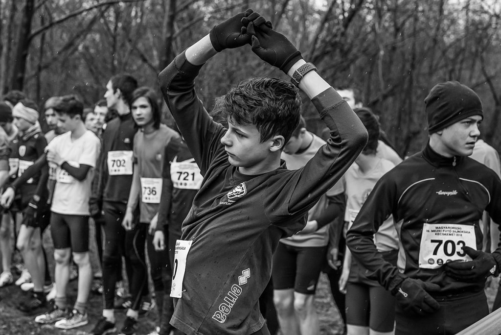 Young runner boy stretching at the startline